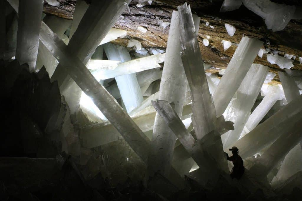 Huge crystal formations in cave with small man