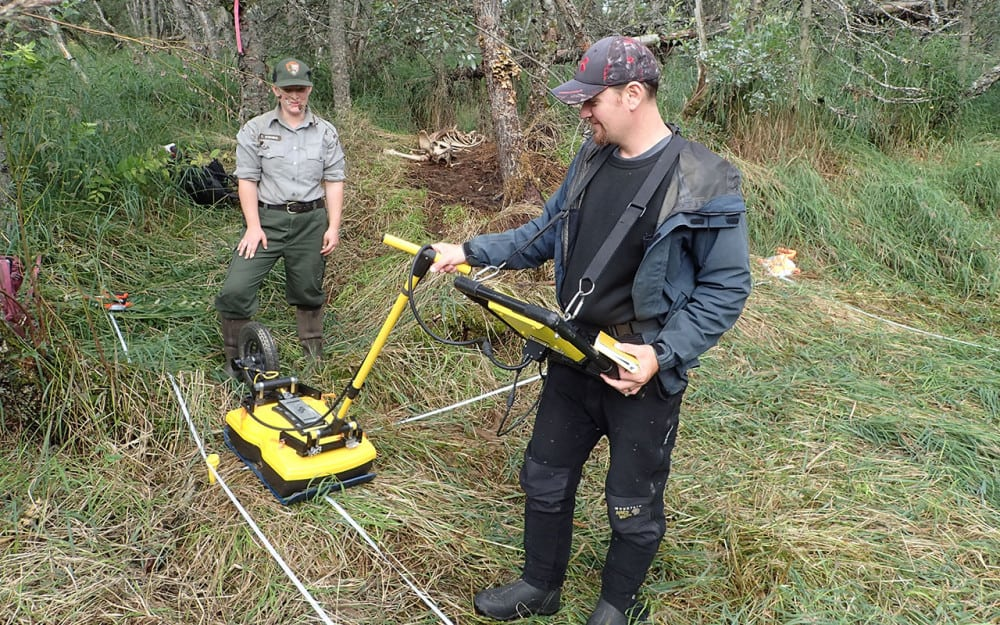 Photo of two men using ground pentetrating radar (GPR)