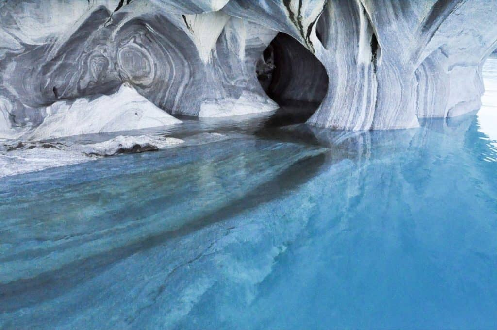 Cave with bright blue water and white and yellow streaks